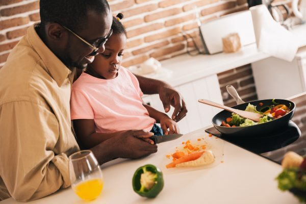 Dad and daughter cutting fresh vegetables for dinner