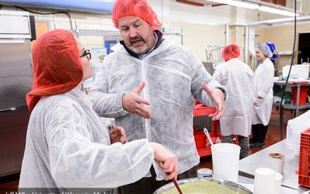 Two people working in a food production kitchen.